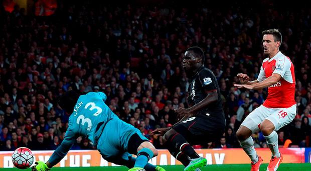 Arsenal's Czech goalkeeper Petr Cech (L) saves a shot by Liverpool's Zaire-born Belgian striker Christian Benteke during the English Premier League football match between Arsenal and Liverpool at the Emirates stadium, north London on August 24, 2015. AFP PHOTO / BEN STANSALL