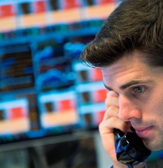 A trader gives a call in the midst of volatile market activity that saw bargain hunters nudging up Asian and European stocks though China continued to suffer