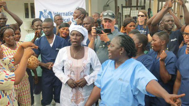 Adama Sankoh (35), centre, who contracted Ebola after her son died from the disease being discharged Credit: AP