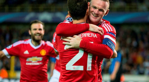 Manchester's Wayne Rooney (R) celebrates with his teammate Ander Herrera after scoring a goal during the UEFA Champions League playoff football match between Club Brugge and Manchester United at Jan Breydel Stadium in Bruges, on August 26, 2015. AFP PHOTO/BELGA/KURT DESPLENTERKURT DESPLENTER/AFP/Getty Images