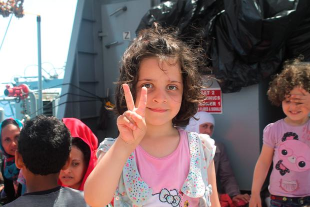A girl smiles as she is taken aboard the LÉ NIAMH Credit: Irish Defence Forces