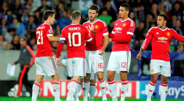 Wayne Rooney, second left, celebrates with teammates after scoring during the Champions League play-off round