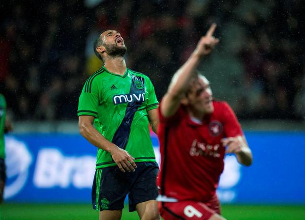 Southampton's Steven Caulker reacts as FC Midtjylland's Morten Duncan Rasmussen (R) celebrates after scoring a goal during their Europa League play-off soccer match at MCH Arena in Herning