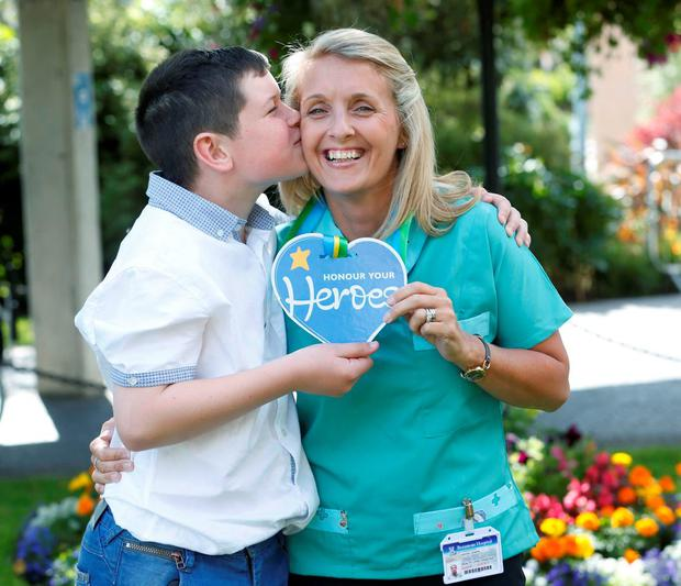 Eoghan McManus (9) presents Deirdre Green with her Honour Your Hero award