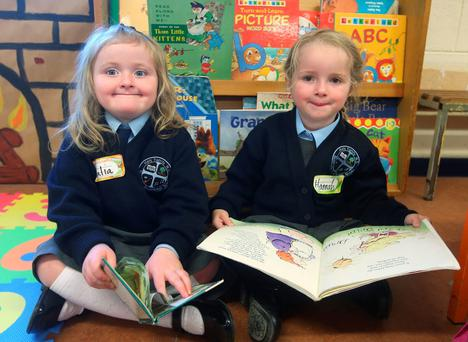 Julia Byrne (5), left, and Hannah Doyle (5) on their first day of school at Holy Family National School, Rathcoole, Dublin, yesterday. Photo: Damien Eagers