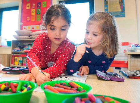 Best of friends: Lucy McKeown and Millie Kenny get out their colouring pencils on their first day at school in Kilcolgan Educate Together national school in Co Galway. Photo: Andrew Downes