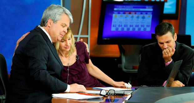 TV7 news morning anchor Kimberly McBroom, centre, gets a hug from visiting anchor Steve Grant, left, as meteorologist Leo Hirsbrunner reflects after their early morning newscast at the station. (AP Photo/Steve Helber)