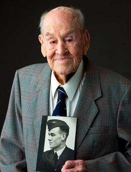 In this June 23, 2015 photo provided by Gordon Royle, his father Paul Royle poses for a photo holding a picture of himself in uniform during World War ll, in Perth, Australia. (Garry Sarre/Gordon Royle via AP)