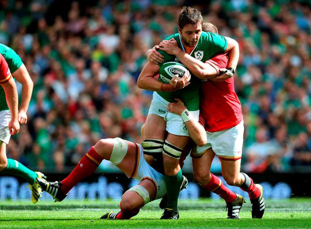 Ireland's Iain Henderson is tackled by Wales' Gethin Jenkins (right) and captain Alun Wyn Jones during the World Cup Warm Up Match at the Aviva Stadium, Dublin. PRESS ASSOCIATION Photo. Picture date: Saturday August 29, 2015. See PA story RUGBYU Ireland. Photo credit should read: Brian Lawless/PA Wire.