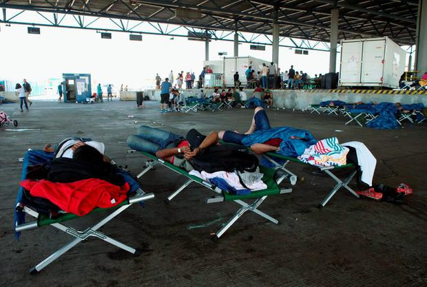 Migrants, who have been picked up within Austria near the border with Hungary, wait at a makeshift camp in Nickelsdorf, Austria, August 29, 2015. About 100,000 migrants, many of them from Syria and other conflict zones in the Middle East, have taken the Balkan route into Europe this year, heading via Serbia for Hungary and Europe's Schengen zone of passport-free travel. Most then move on to richer countries such as Austria and Germany. REUTERS/Heinz-Peter Bader