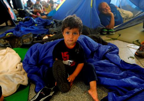 A migrant girl sits on the floor while waiting to leave Hungary outside a train station in Budapest, Hungary August 29, 2015. About 100,000 migrants, many of them from Syria and other conflict zones in the Middle East, have taken the Balkan route into Europe this year, heading via Serbia for Hungary and Europe's Schengen zone of passport-free travel. Most then move on to richer countries such as Austria and Germany. REUTERS/Laszlo Balogh