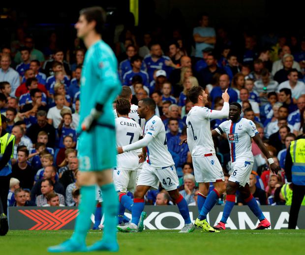 Chelseas Belgian goalkeeper Thibaut Courtois reacts as the Crystal Palace team celebrate Crystal Palaces second goal during the English Premier League football match between Chelsea and Crystal Palace at Stamford Bridge in London on August 29, 2015. Crystal Palace won the game 2-1. AFP PHOTO / IAN KINGTON
