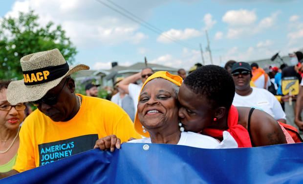 Revia Roman, right, kisses Mary Evans, as she marches with members of the NAACP during a second-line parade to commemorate the 10th anniversary of Hurricane Katrina in the Lower 9th Ward in New Orleans, Saturday, Aug. 29, 2015. Residents in Mississippi and Louisiana were marking the somber anniversary by paying homage to those who died in Katrina, to thank those who came to rebuild and celebrate how far the region has come since the hurricane struck.(AP Photo/Gerald Herbert)