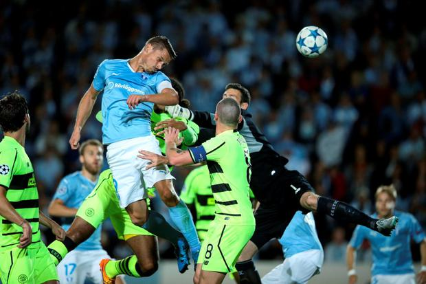 Malmo FF's Markus Rosenberg (blue) heads the ball to score the opening goal past Celtic's goalkeeper Craig Gordon (R) and Scott Brown (8) during their Champions League play-off second leg soccer match at Malmo New Stadium
