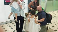NO REGRETS: Janet and Eugene Bennis, being greeted at the airport by their daughter and granddaughters Saoirse, Teegan and Isabel and Alexia, absolutely love their new life in Brisbane where they get to see their grandchildren every day