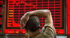 CRASH: A Chinese day trader watches a stock fall at a local brokerage house as the crisis hit hard early last week