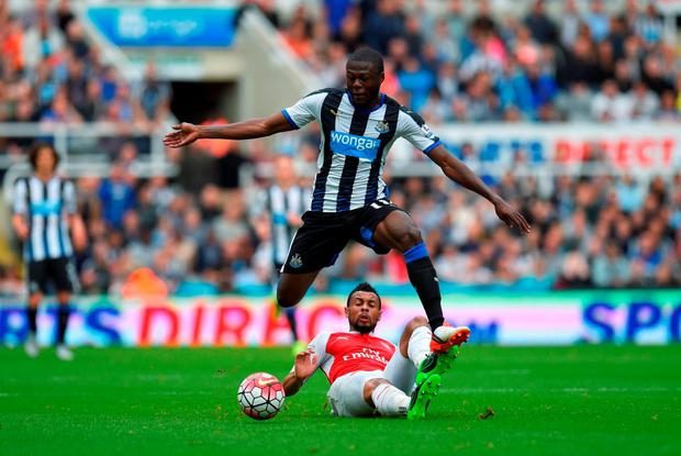 Chancel Mbemba of Newcastle United and Francis Coquelin of Arsenal compete for the ball