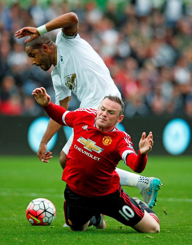 Swansea City's Ashley Williams makes a last-ditch tackle on Wayne Rooney