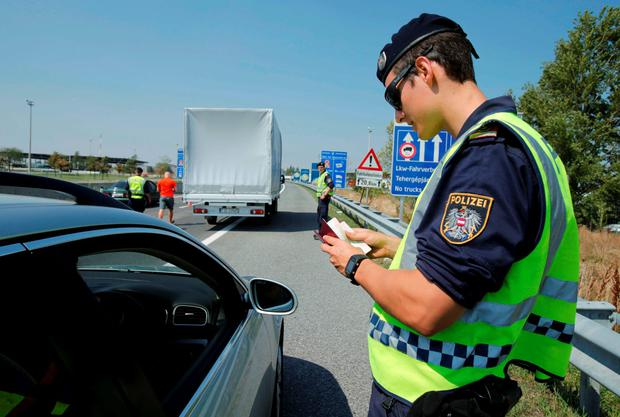 An Austrian police officer checks documents of a car driver arriving to Austria at a checkpoint in the village of Nickelsdorf, Austria, August 31, 2015. REUTERS/Heinz-Peter Bader