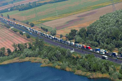 Trucks stand in a queue along a highway near the Austrian border in Hegyeshalom, Hungary, August 31, 2015. REUTERS/Laszlo Balogh