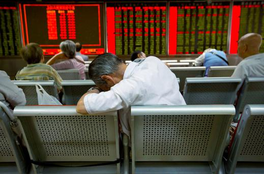 Chinese investors monitor stock prices at a brokerage house in Beijing