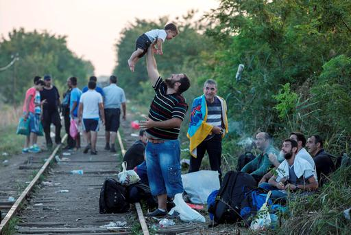 A migrant, hoping to cross into Hungary, plays with a child along a railway track outside the village of Horgos in Serbia, towards the border it shares with Hungary Credit: REUTERS/Marko Djurica
