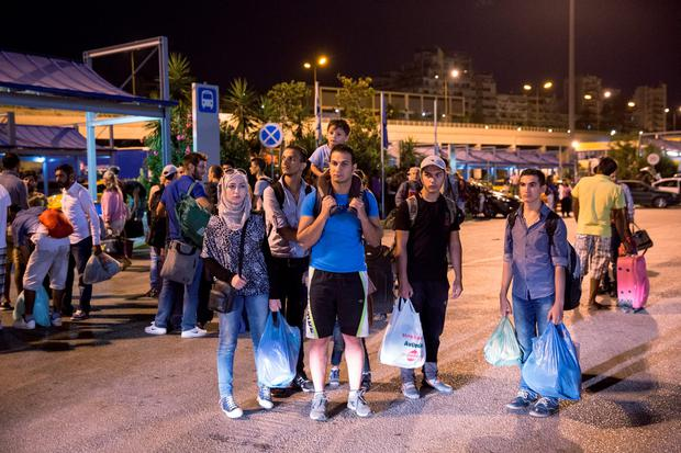 Migrants along with European tourists wait to board a bus heading to Athens Credit: Dan Kitwood/Getty Images
