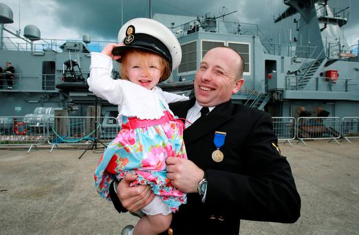 Petty Officer Sean Barrett with his daughter Mairead (20 months) beside the LÉ James Joyce after the Naming and Commissioning Ceremony in Dun Laoghaire