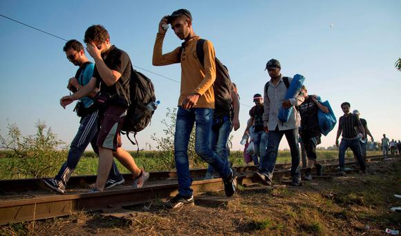 A group of migrants crosses the border walking on the railway track from Serbia into Hungary Credit: AP Photo