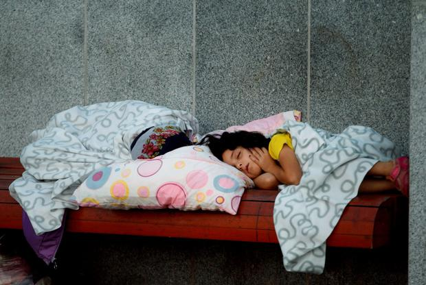 A young girl sleeps on a bench as migrants rest near the Keleti Railway Station in Budapest, Hungary, Wednesday, Sept. 2, 2015, after police stopped them from getting on trains to Germany. (AP Photo/Petr David Josek)