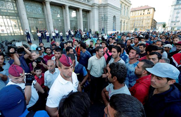 Hungarian policemen talk to some of hundreds of migrants waiting near the Keleti Railway Station in Budapest, Hungary, Wednesday, Sept. 2, 2015, after police stopped them from getting on trains to Germany. AP Photo/Petr David Josek)