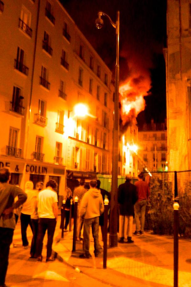 People stand in the street below as flames and smoke billow out of the window of an apartment building Credit: JEAN-RAPHAEL BOURGE/AFP/Getty Images