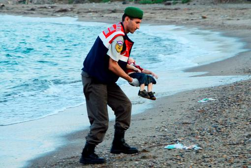 A Turkish gendarmerie carries a young migrant named Aylan, who tragically drowned in a failed attempt to sail to the Greek island of Kos, in the coastal town of Bodrum