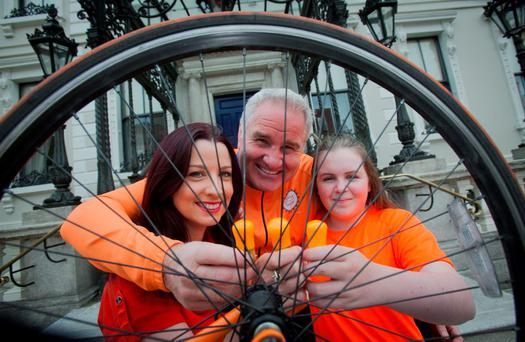 Event organiser Aisling Riordan, broadcaster Brent Pope and student Emma Daly promote the Cycle Against Suicide campaign which will see both homes and famous Irish landmarks lit up in orange.