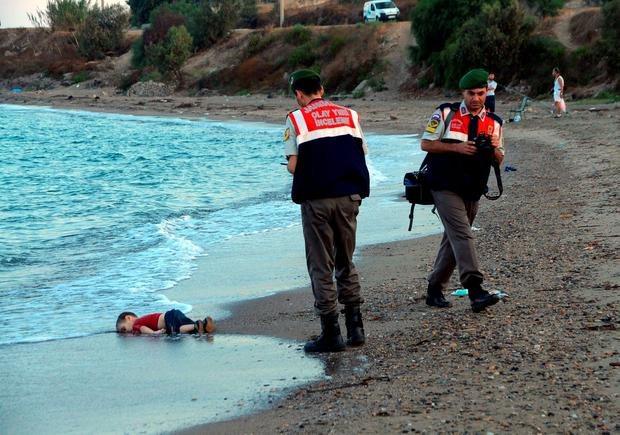 Police officers investigate the scene before carrying the lifeless body of Aylan Kurdi away from the sea Credit: AP