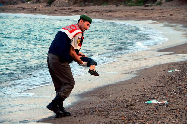 A Turkish border guard carries the lifeless body of Aylan Kurdi (3) after a number of migrants died and others were reported missing when boats carrying them to the Greek island of Kos capsized near Bodrum in Turkey.