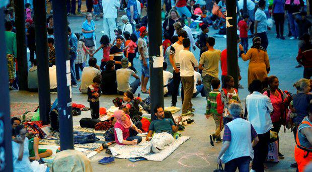 Hungarians walk by as refugees rest at a makeshift camp in an underground station near the Keleti train station in Budapest, Hungary September 2, 2015