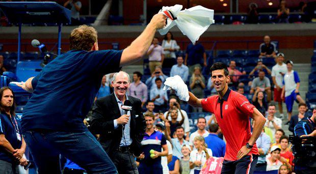 Novak Djokovic of Serbia (R) dances on the court with a fan after defeating Andreas Haider-Maurer of Austria during their US Open 2015 second round men's singles match at the USTA Billie Jean King National Center September 2, 2015 in New York