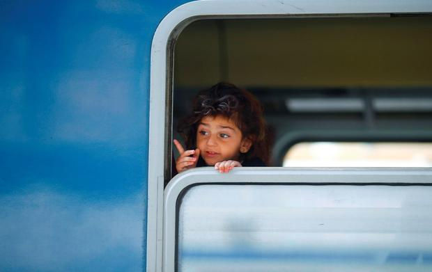 A migrant girl looks from a train's window at the Keleti train station in Budapest, Hungary, September 3, 2015 as Hungarian police withdrew from the gates after two days of blocking their entry. REUTERS/Leonhard Foeger