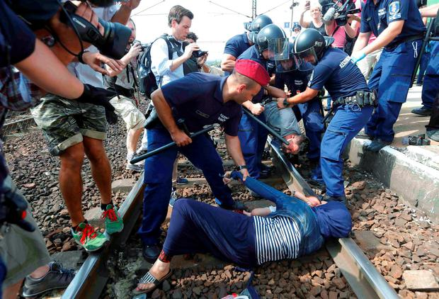 Hungarian policemen detain migrants in Hungary Credit: REUTERS/Laszlo Balogh