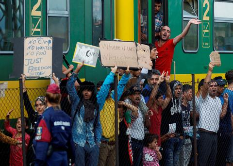 People shout slogans outside a train that was stopped in Bicske, Hungary, Friday, Sept. 4, 2015. Over 150,000 migrants have reached Hungary this year, most coming through the southern border with Serbia. Many apply for asylum but quickly try to leave for richer EU countries. (AP Photo/Petr David Josek)