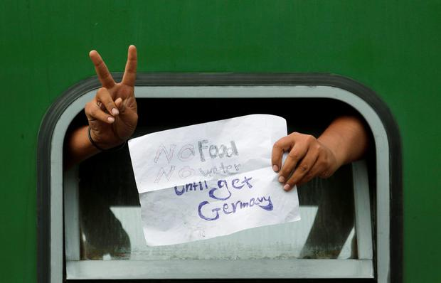 A man displays a sign out of a window of a train that was stopped in Hungary Credit: AP Photo/Petr David Josek