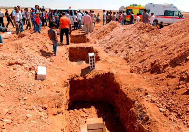 Three graves that were dug for the two Syrian toddlers and their mother, all of whom drowned as they were trying to reach Greece, are pictured during their funeral in the Syrian border town of Kobani September 4, 2015. REUTERS/Rodi Said