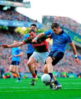 Dublin's Kevin McManamon shoots to score his side's third goal despite the attempts of Keith Higgins