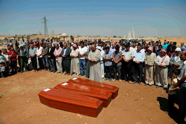 Syrian Kurds pray behind the coffins of the members of Kurdi family, two Syrian toddlers and their mother who drowned while they were trying to reach Greece, during a funeral ceremony in the northern border town of Kobani, Syria