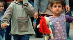 Suffer the little children: Migrants walk at a railway station in Munich, Germany, yesterday. Austria and Germany threw open their borders to thousands of exhausted migrants yesterday, bussed to the Hungarian border by a right-wing government that had tried to stop them but was overwhelmed by the sheer numbers reaching Europe's frontiers