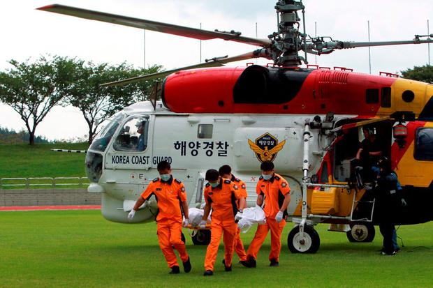South Korean Coast Guard personnel carry the body of a passenger who was onboard a boat called Dolgorae, or Dolphin, which capsized at the sea off the southern island of Jeju in Heanam, South Korea, September 6, 2015. REUTERS/Park Ji-ho/Yonhap