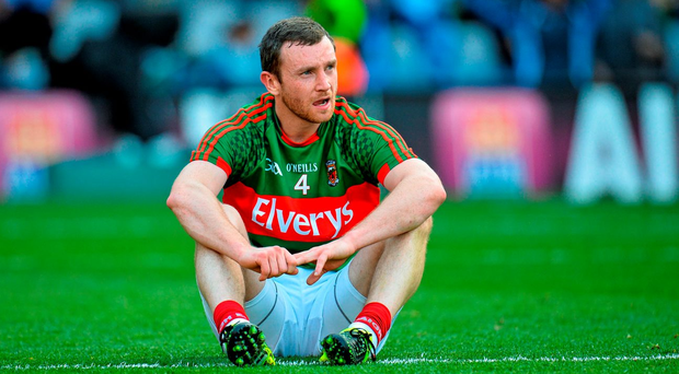 Mayo's dejected Keith Higgins sits on the Croke Park pitch after the game