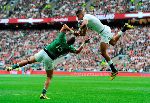 England's Anthony Watson climbs above Simon Zebo to collect a cross field ball on his way to scoring his side's second try at Twickenham