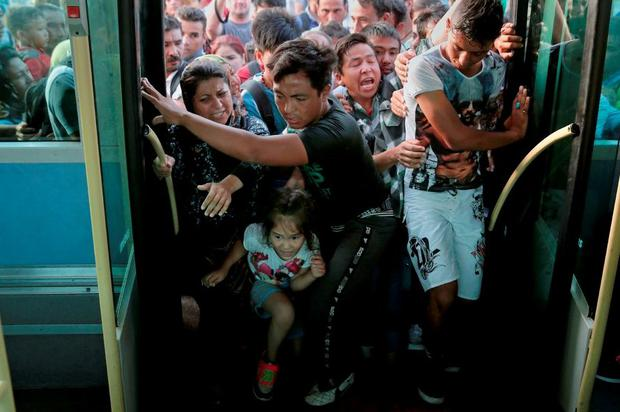 Refugees push each other as they try to board a bus following their arrival onboard the Eleftherios Venizelos passenger ship at the port of Piraeus, near Athens, Greece, yesterday. Photo: Reuters/Alkis Konstantinidis